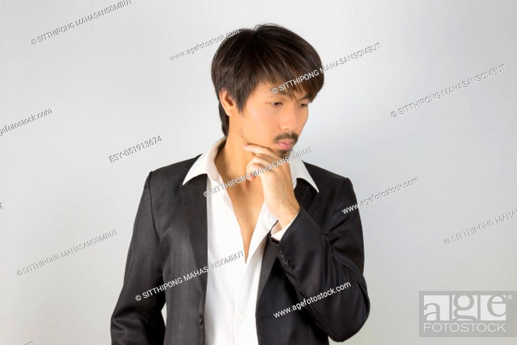 Photo de stock: Portrait Businessman in Black Suit Fashion Touch Chin Pose. Portrait businessman wear white shirt and suit in smart pose style.