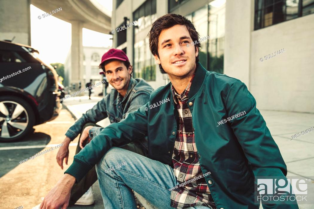 Stock Photo: Two smiling young men sitting on sidewalk.