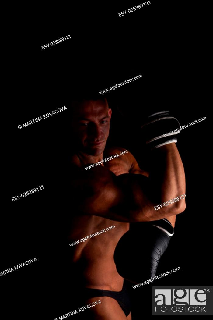 Stock Photo: Fighter. Young sexy muscular shirtless man with boxing gloves looking into camera isolated on black background. Sport and fitness.