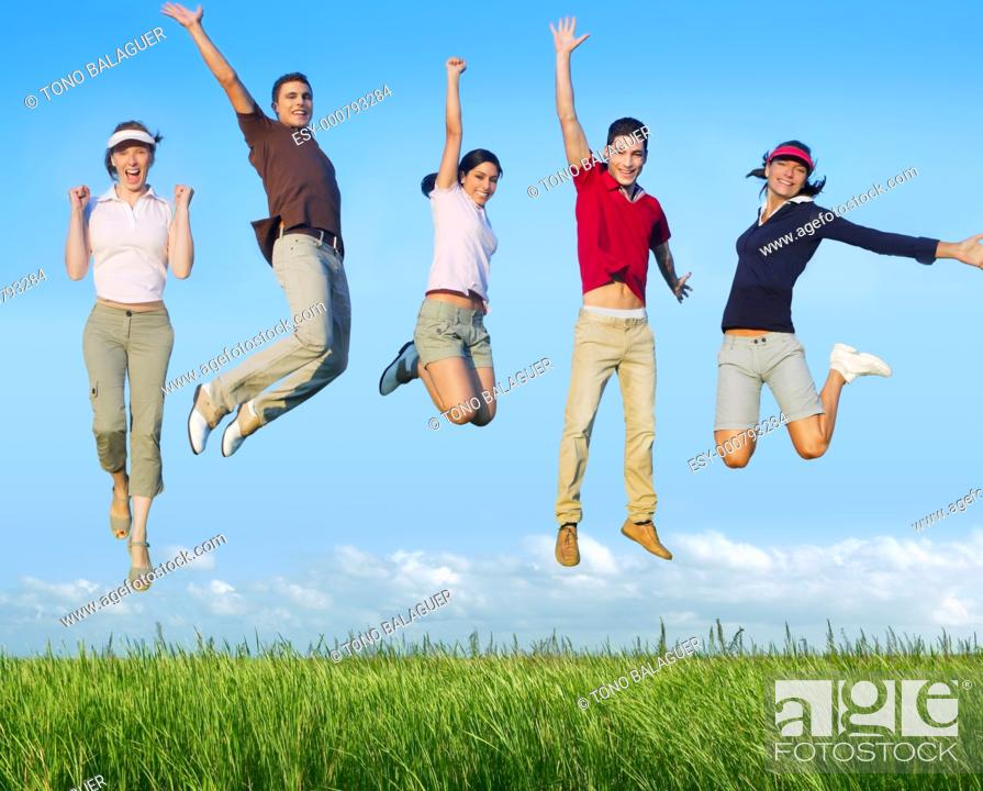 Stock Photo: Jumping young people happy group in meadow blue sky outdoor.