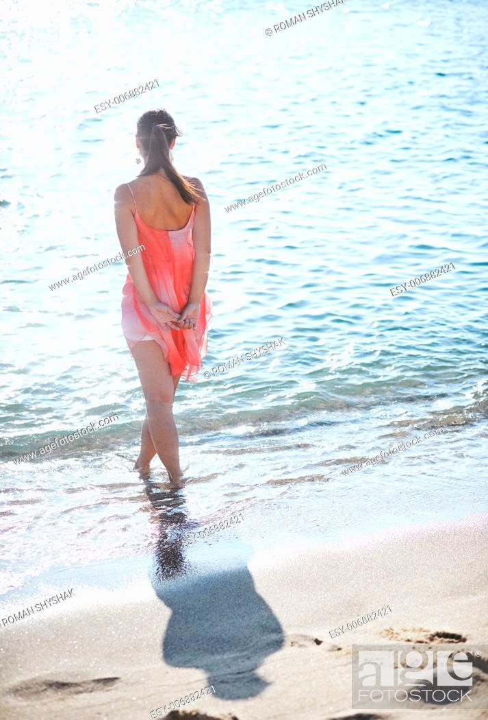 Stock Photo: A young woman in sea water. She is looking out over sea.