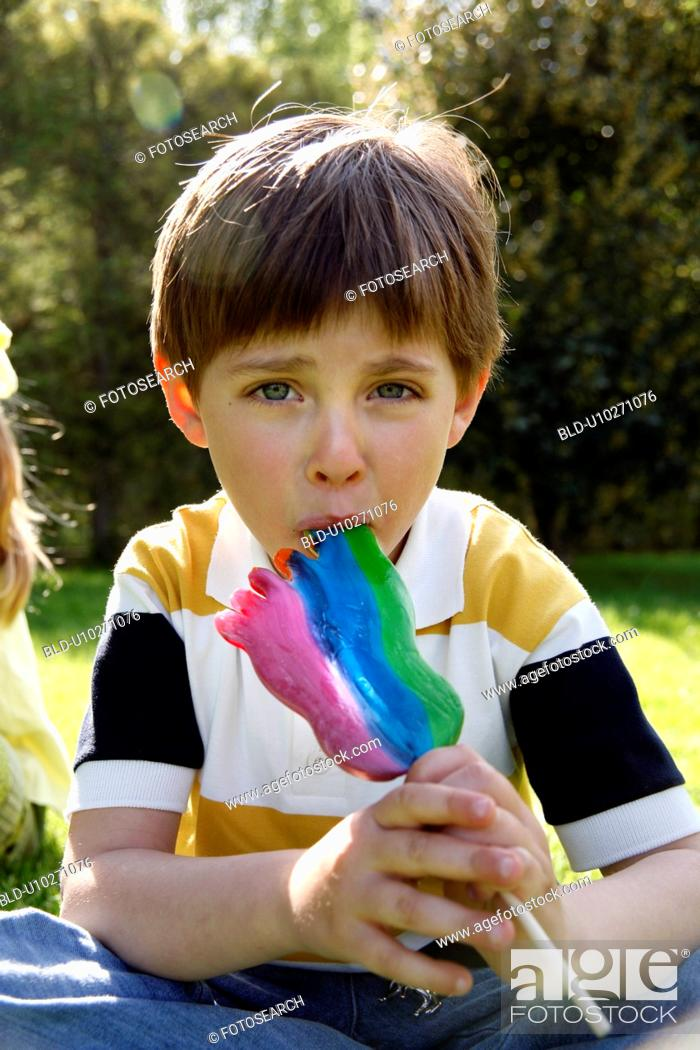 Stock Photo: Young boy licking a lollipop.