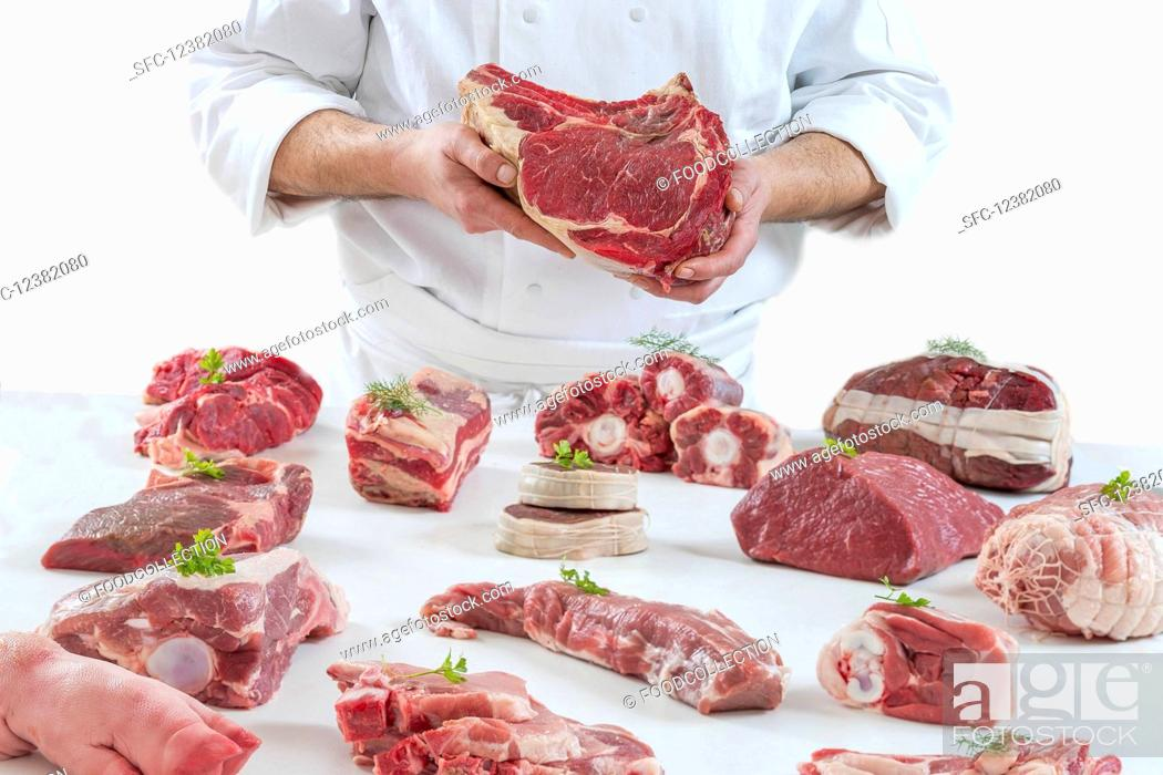 Stock Photo: A chef presenting different types of fresh raw meat.