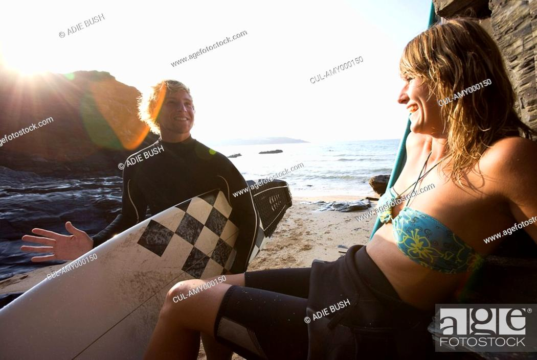 Stock Photo: Couple laughing at the beach with man holding a surfboard.