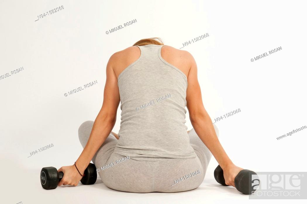 Stock Photo: Young woman, redhead, sitting, exercising with weights at the gym.