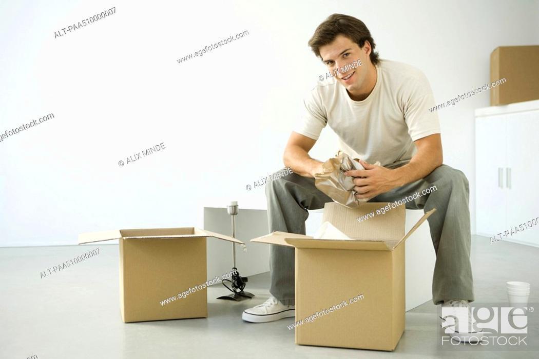 Stock Photo: Man unpacking boxes, sitting on bench, smiling at camera.
