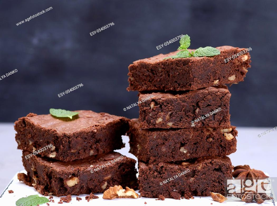 Stock Photo: stack of baked square pieces of chocolate brownie pie with walnuts, close up.