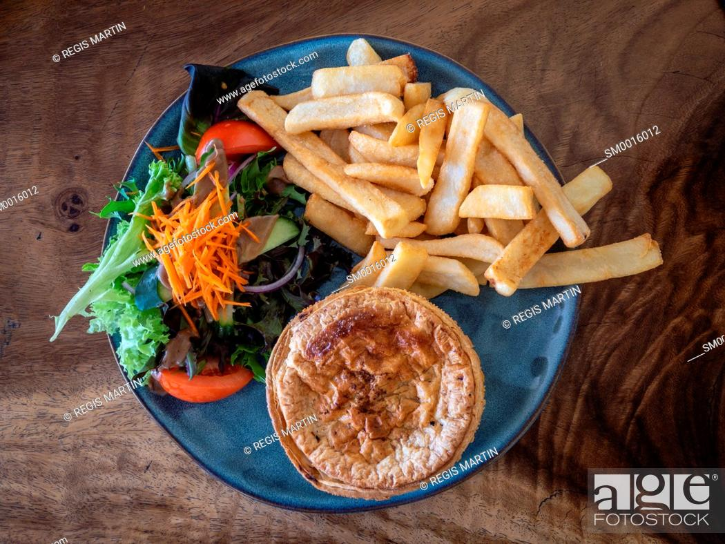 Stock Photo: Typical Australian pub meal a meat pie with salad and fries.