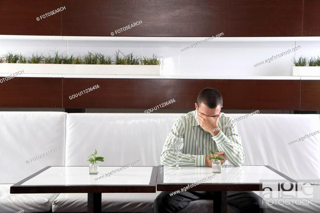 Stock Photo: Stressed businessman leaning on hand in restaurant.