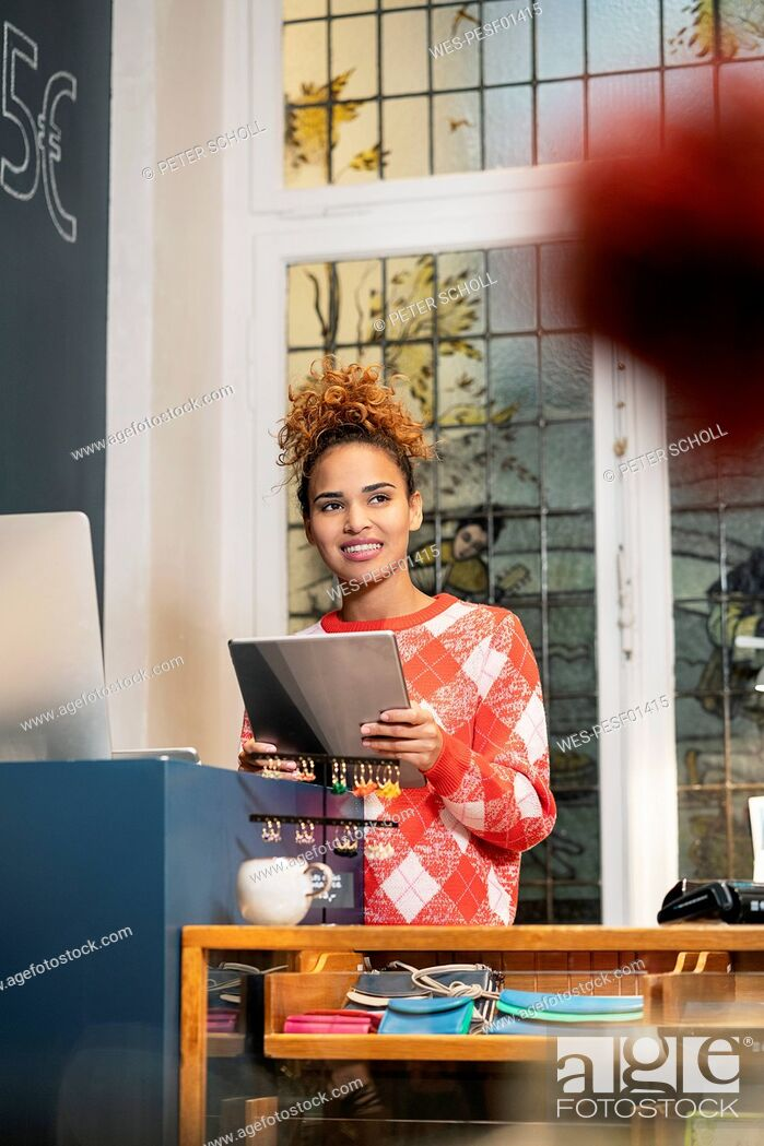 Stock Photo: Young woman working in fashion store, using ldigital tablet.