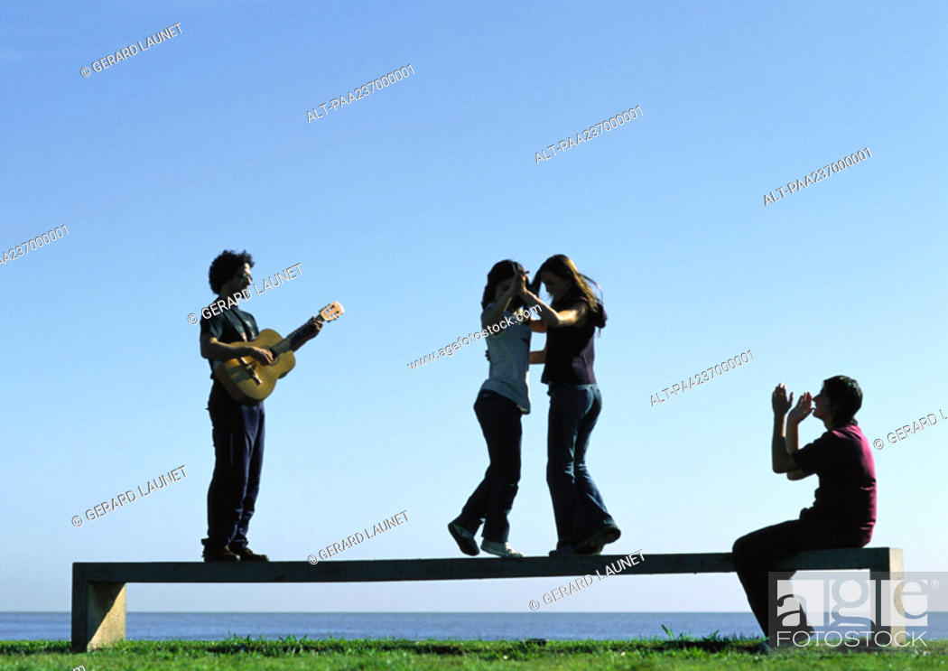 Stock Photo: Young people playing on bench near water.