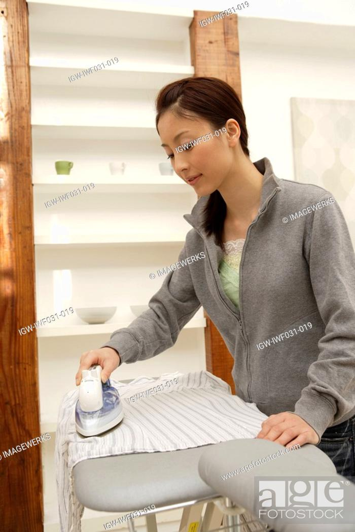 Stock Photo: View of a young woman ironing a shirt.
