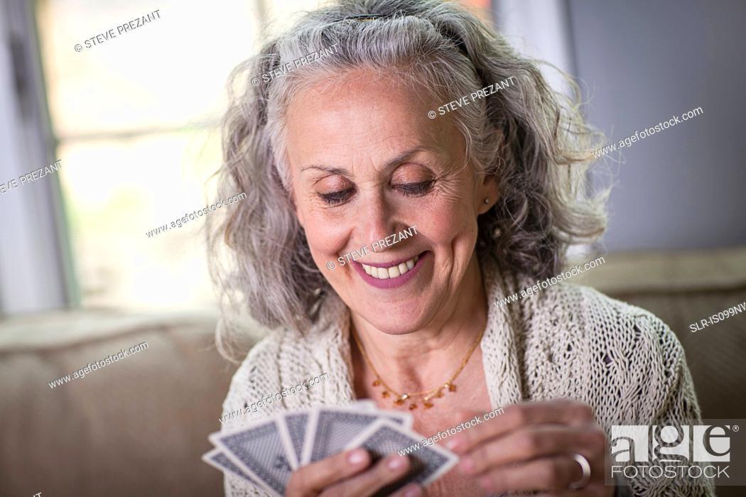 Stock Photo: Senior woman playing card game at home.