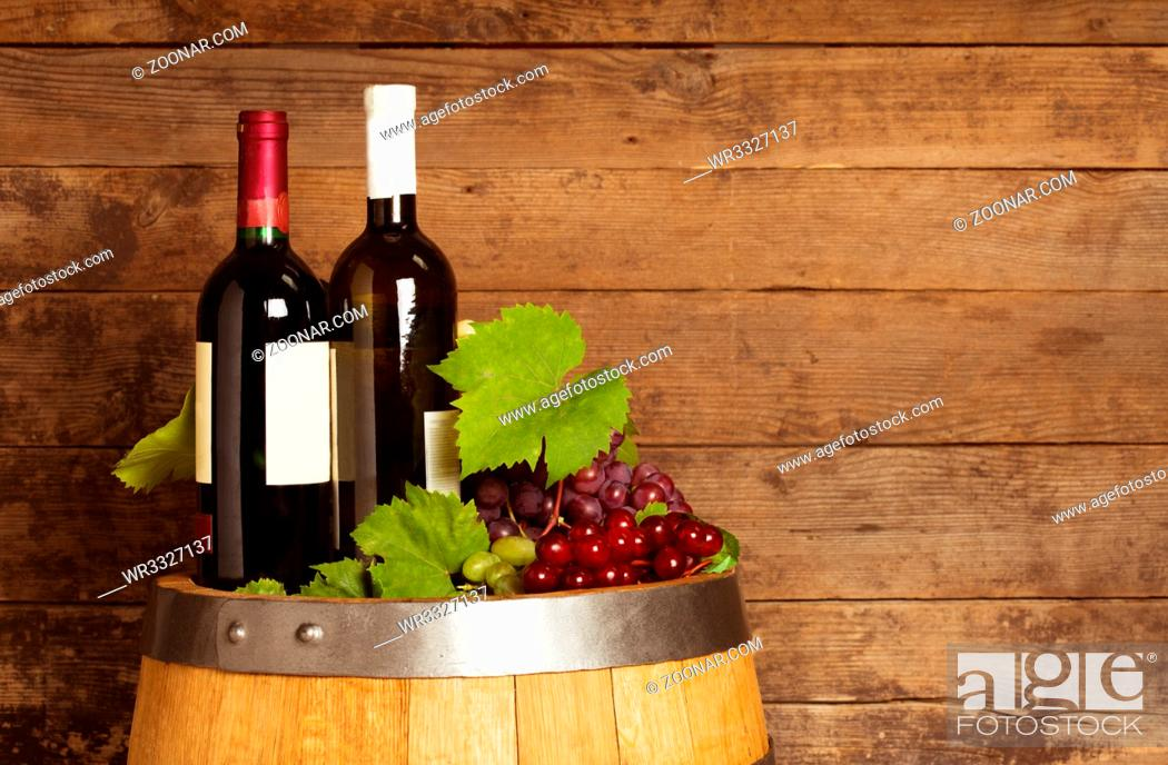 Photo de stock: Bottles of wine on the oak barrel over old shabby wooden background.