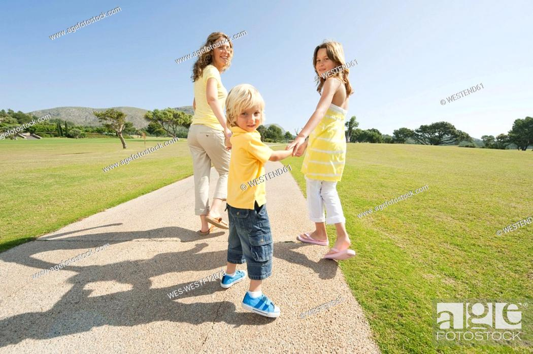 Stock Photo: Spain, Mallorca, Mother and children 4-5, 10-11 having a walk.