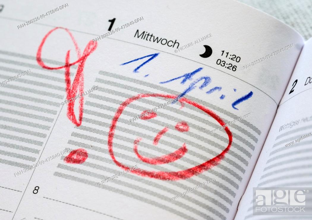 Stock Photo: 24 March 2020, Berlin: In a calendar on April 1st there is a warning exclamation mark and a smiley. Photo: Jens Kalaene/dpa-Zentralbild/dpa.