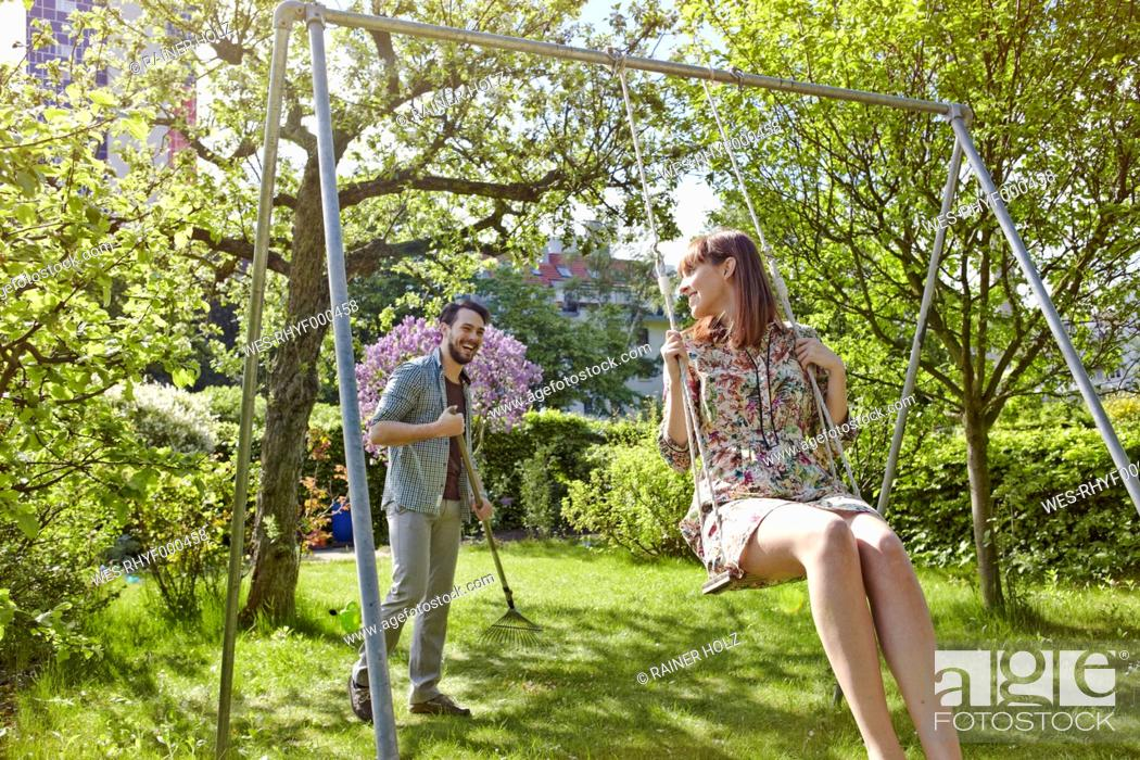 Stock Photo - Germany, Cologne, Young woman swinging while man raking lawn  in background