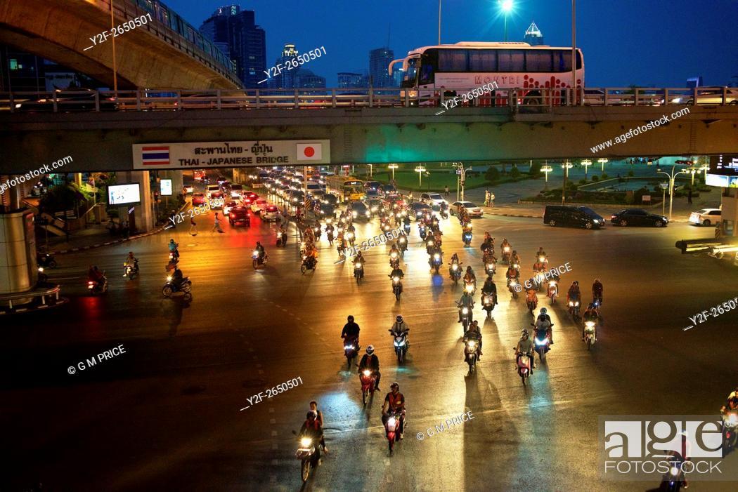 Imagen: pack of motorcycles crosses intersection on Rama IV road at dusk, Bangkok.