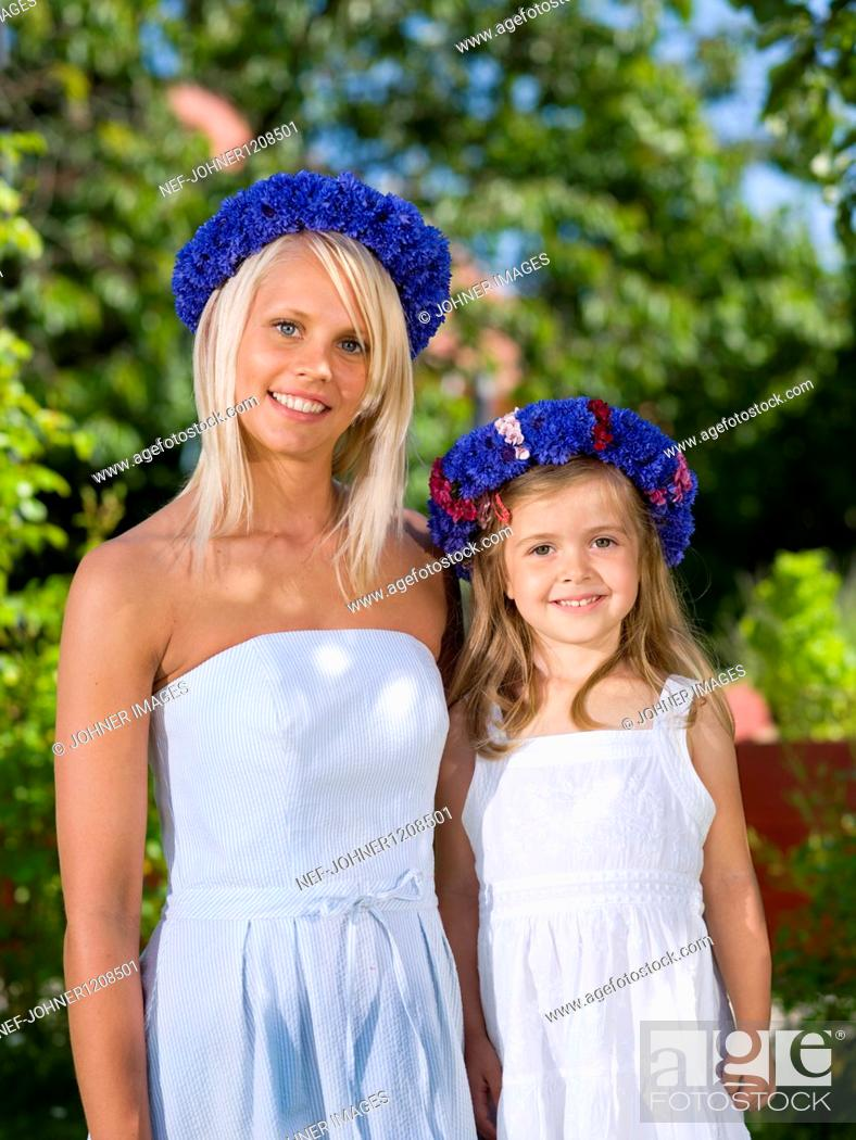 Stock Photo: Mother and daughter standing in garden, portrait, close-up.