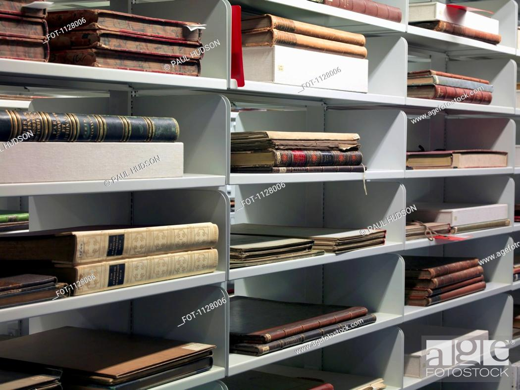 Stock Photo: Detail of old books on shelves in a library.