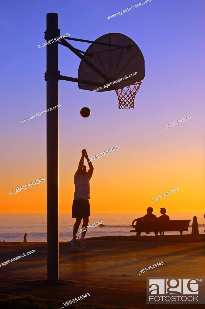 Imagen: A man takes a jump shot at a court near the seashore in Laguna Beach.