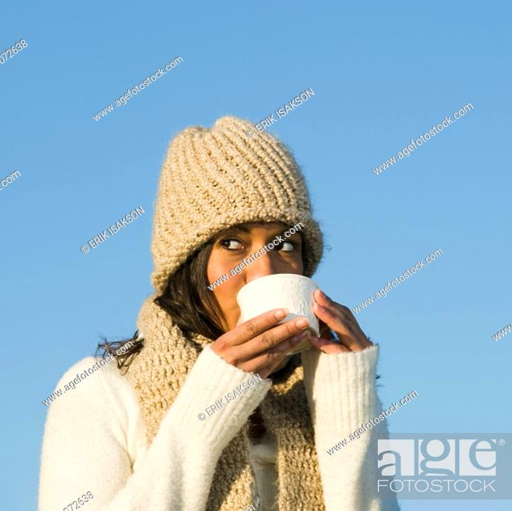 Stock Photo: Mixed race woman drinking coffee outdoors.