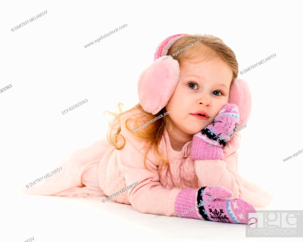 Stock Photo: Little happy pretty girl in winter clothes lies on a white background. 3 year old.