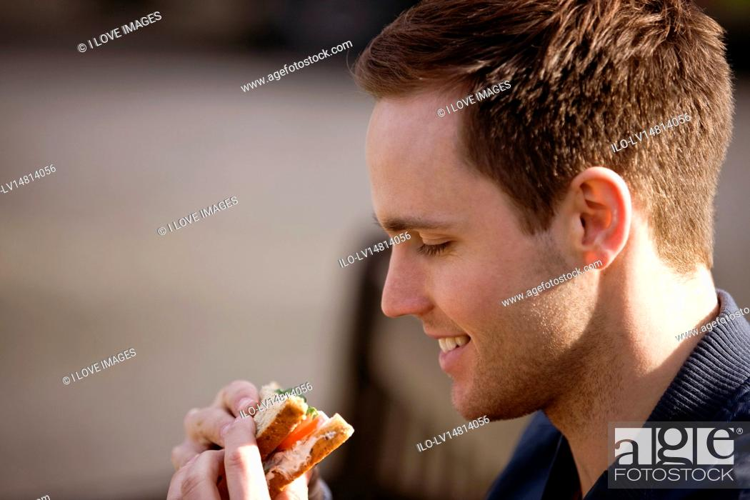 Stock Photo: A young man sitting on a bench, eating a sandwich.