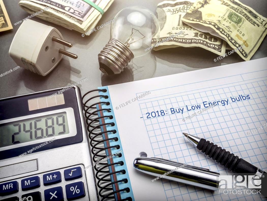 Stock Photo: Calculator and money next to a light bulb, the concept of energy saving.