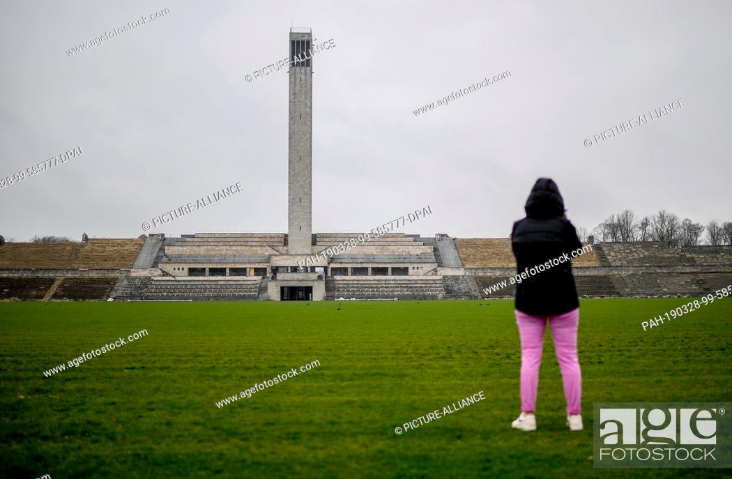 Stock Photo: 28 March 2019, Berlin: A young woman photographs the bell tower on the edge of an event on the future and perspective of the Olympic Park.