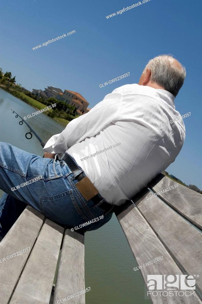 Stock Photo: Rear view of a senior man sitting on a bench at the lakeside and fishing.