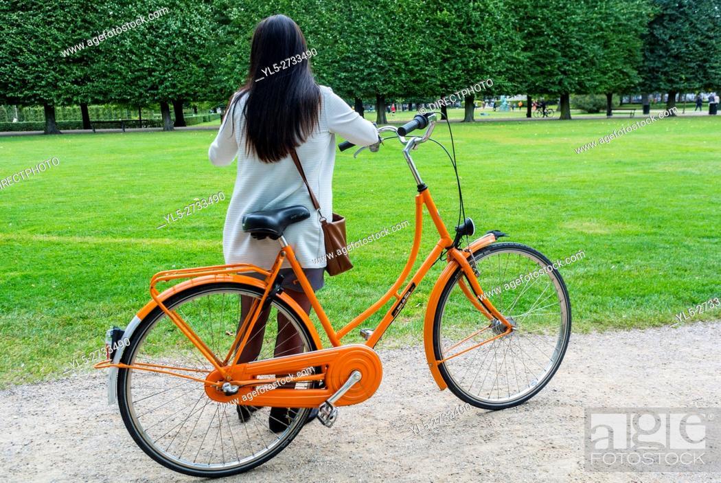 Imagen: Copenhagen, Denmark, Woman with Bicycle in Public Park Scene, King's Garden, Kongens Have.