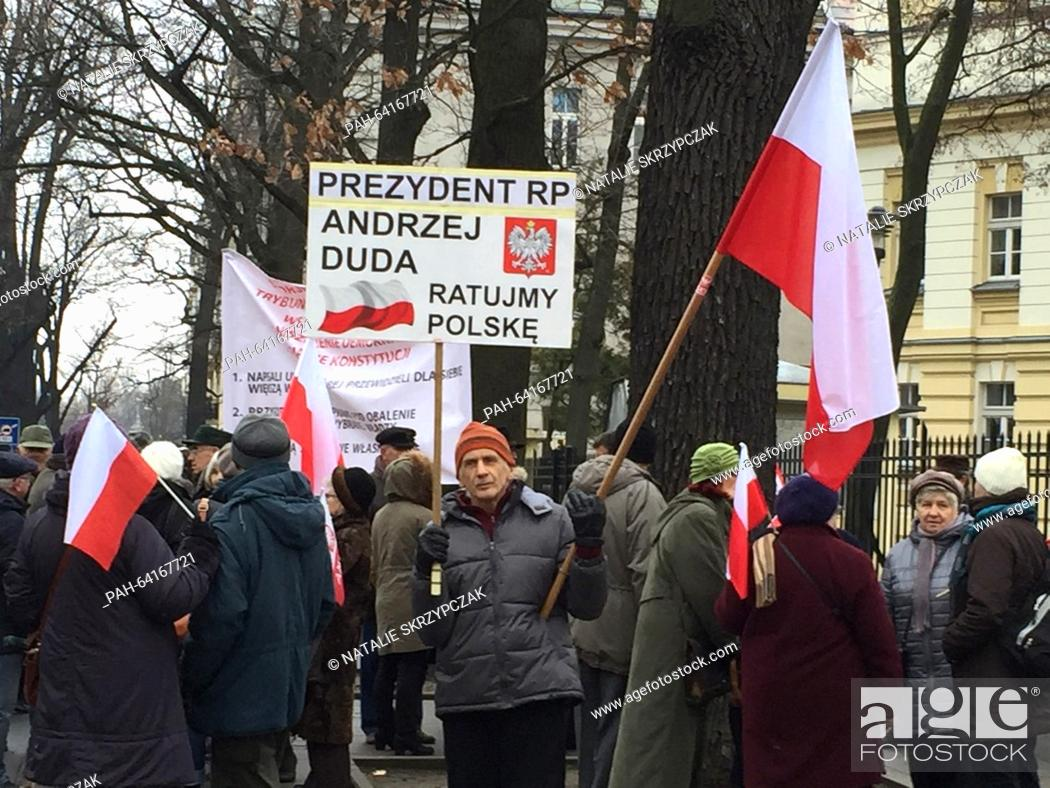 Stock Photo: A small group of pro-government demonstrators carry a sign that reads 'President Andrzej Duda, let us save Poland' during a rally held in front of the.