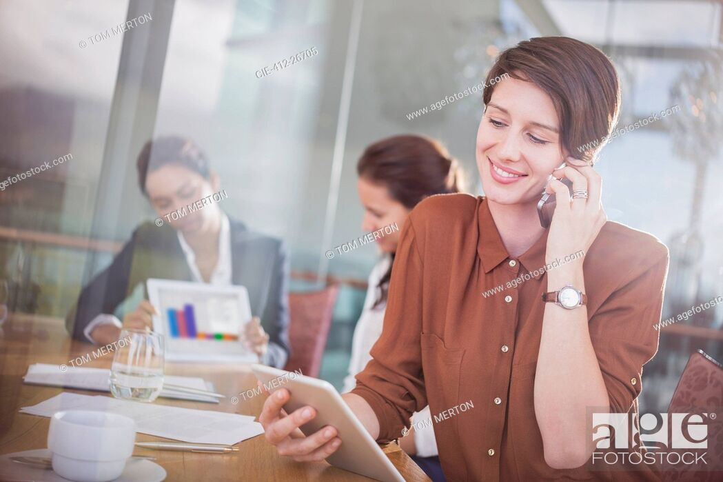Stock Photo: Businesswoman talking on cell phone and using digital tablet in office.