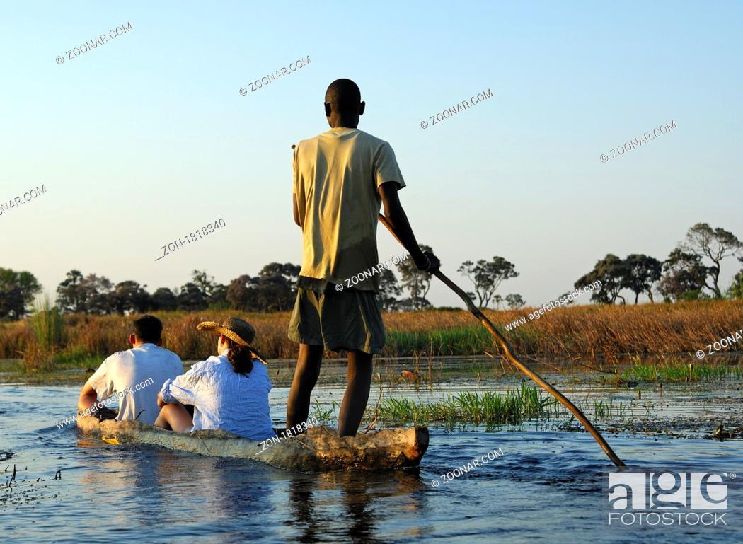 Stock Photo: Kahnfahrer mit Touristen im traditionellen Mokoro Einbaum auf Exkursion im Okavango Delta, Botswana / Poler with tourists in a traditional mokoro logboat on.