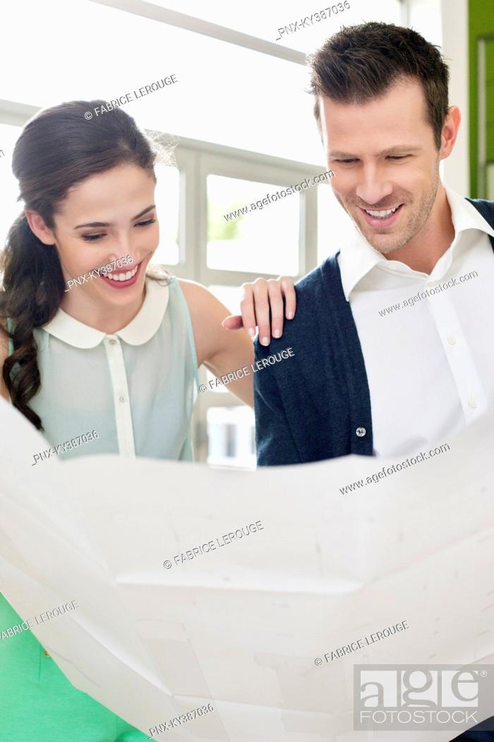 Stock Photo: Couple reading a blueprint.