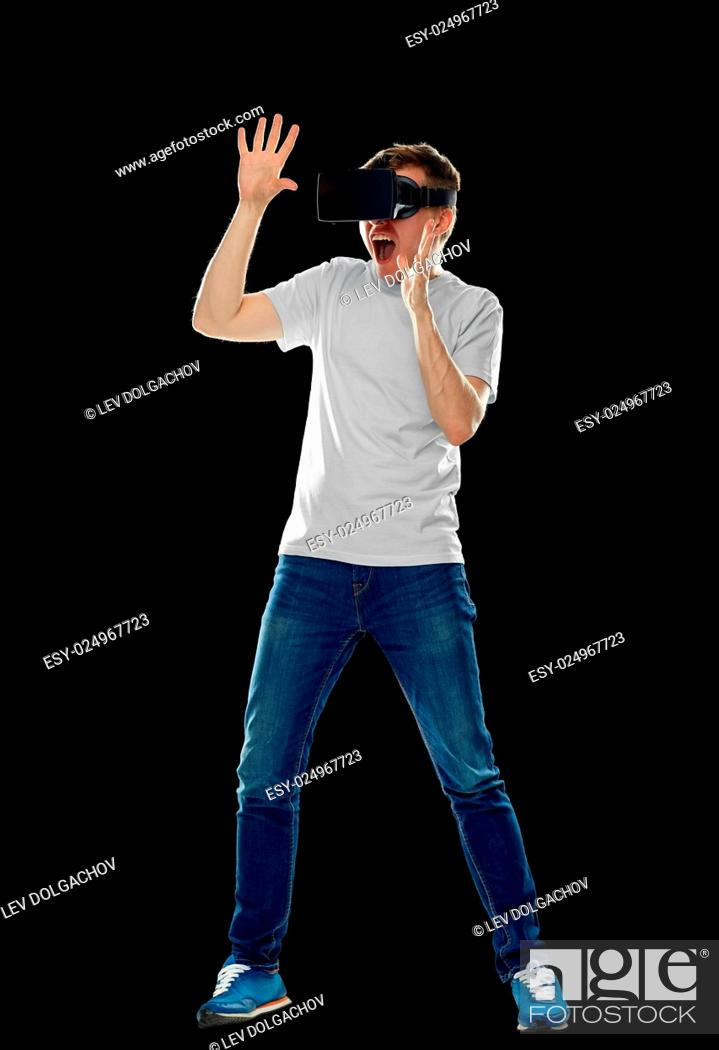 Stock Photo: 3d technology, virtual reality, entertainment, cyberspace and people concept - scared young man with virtual reality headset or 3d glasses playing game and.
