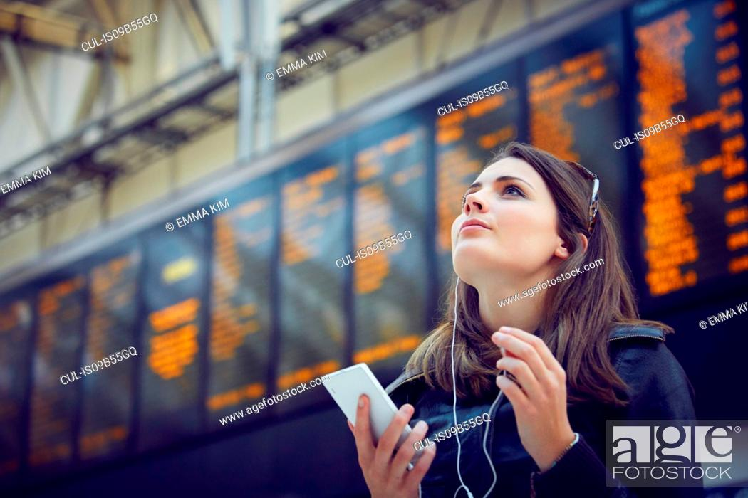 Stock Photo: Woman looking at departure information, London, UK.