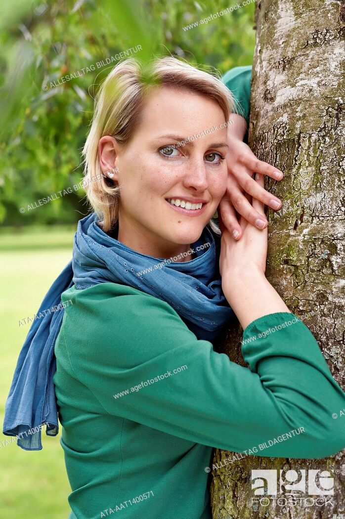 Stock Photo: Woman leaning against a tree.