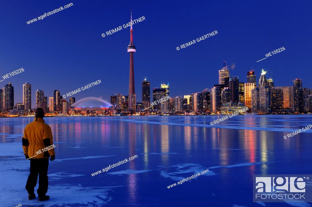 Stock Photo: Man standing on frozen Lake Ontario watching Toronto city skyline light up at dusk.