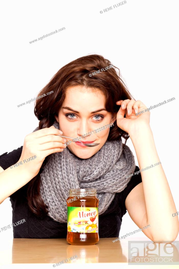 Stock Photo: A beautiful young woman, lady, girl, cold, runny nose, headache, cup of tea with honey, spoon, scarf CTK Photo/Rene Fluger.