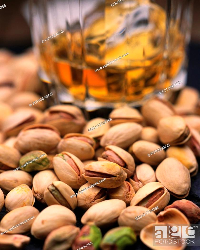 Stock Photo: Closed Up Image of Several Pistachios Next to A Glass With Beer, Differential Focus.