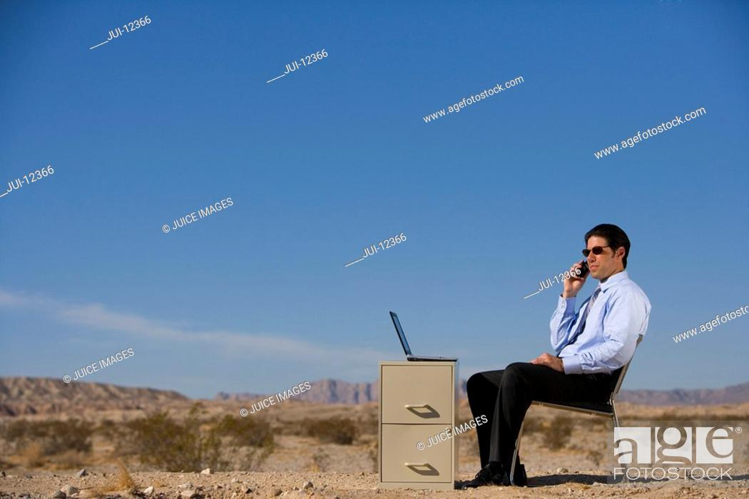 Stock Photo: Businessman working in desert, using mobile phone, side view.