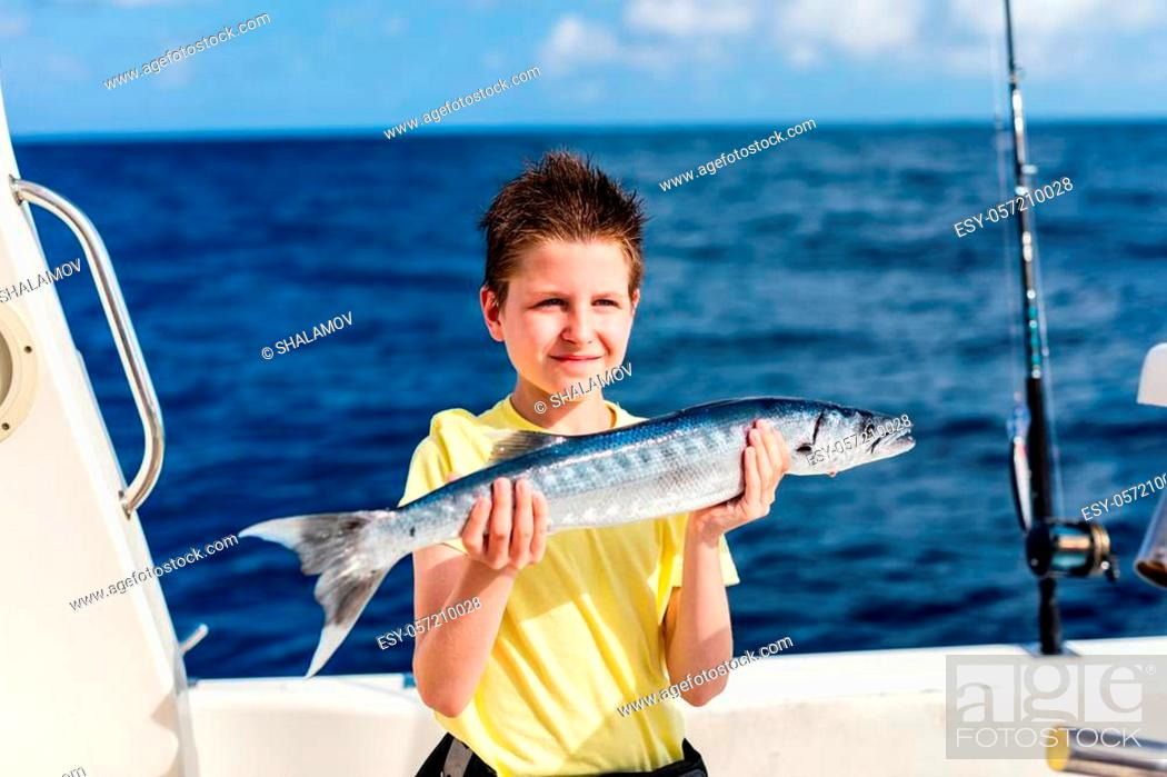 Stock Photo: Lucky teenage boy holding barracuda proud with the catch on boat deck.