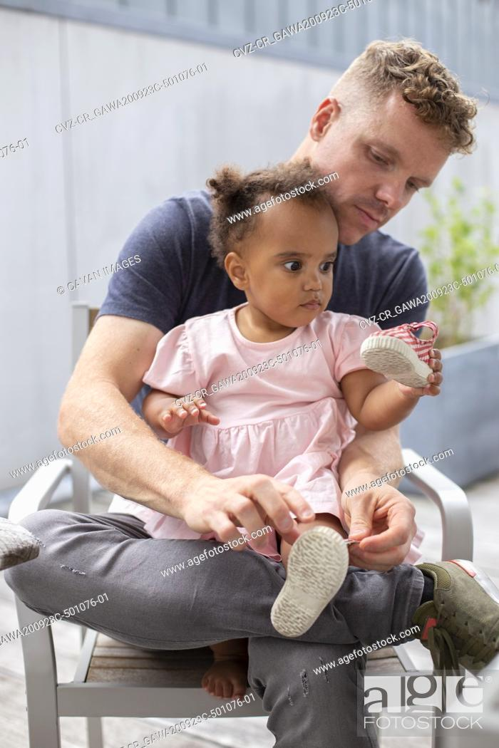 Stock Photo: A dad helping his young daughter put her shoes on.