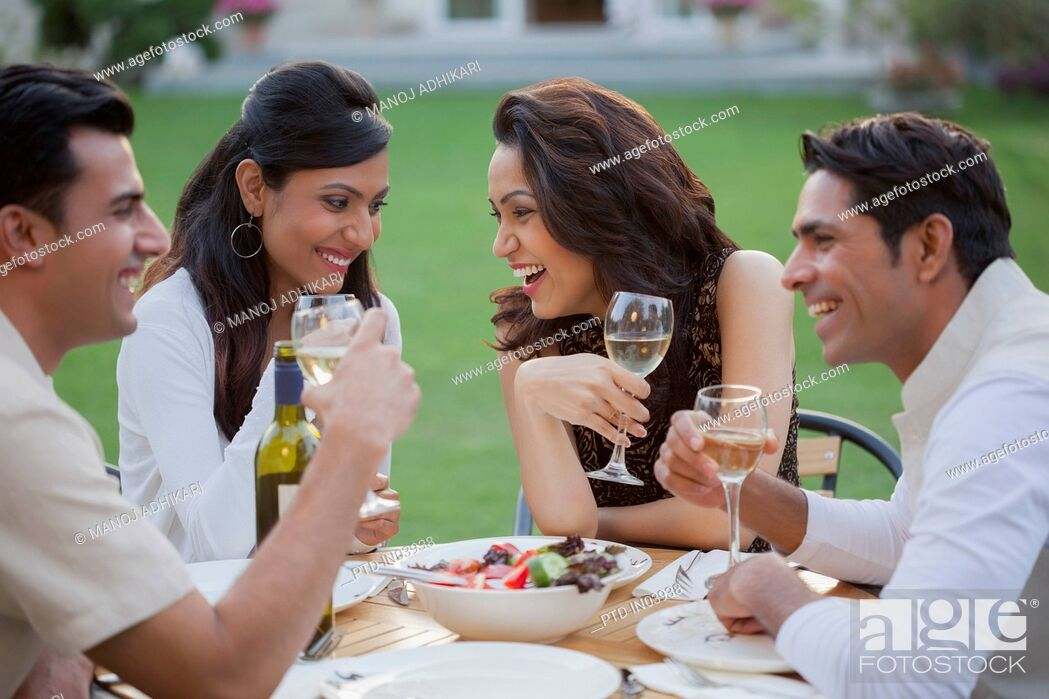 Stock Photo: India, Friends drinking wine at table on backyard.