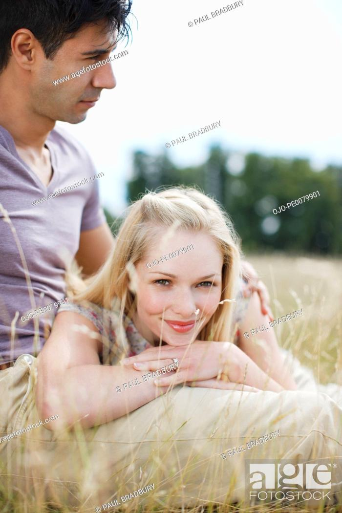 Stock Photo: Smiling woman laying on man's lap in rural field.