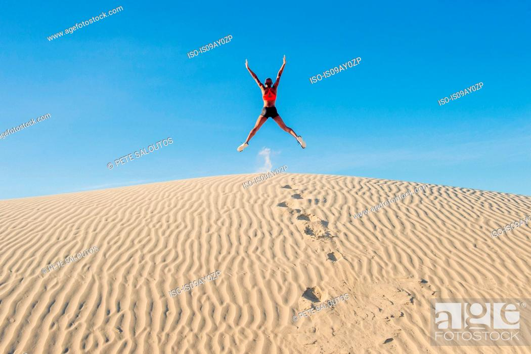 Stock Photo: Runner jumping up with arms and legs outstretched in desert, Death Valley, California, USA.