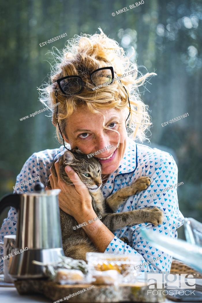 Imagen: Blonde young mature woman with glasses in pyjamas at home in breakfast time, reading a magazine and having a moment with his cat.