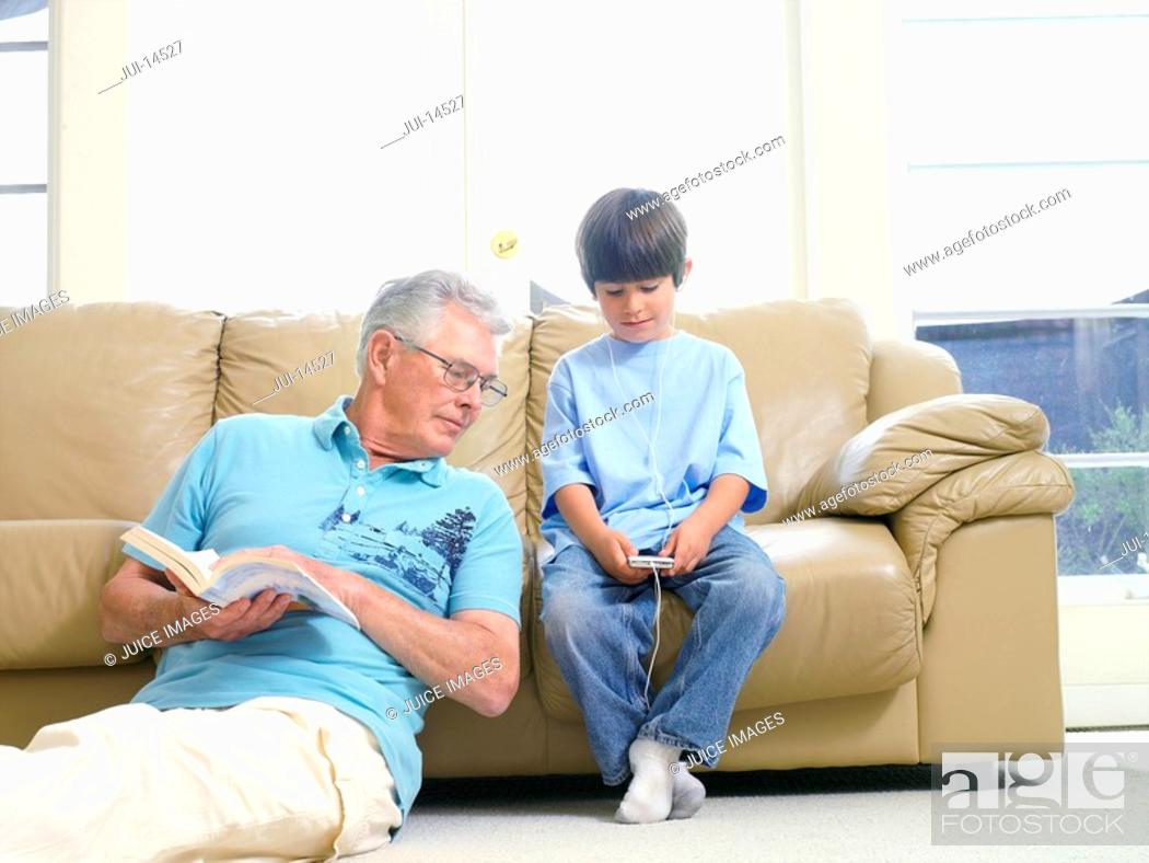 Stock Photo: Grandfather with book looking at grandson's 7-9 MP3 player.